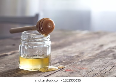 Honey dripping from dipper into jar on old wooden table