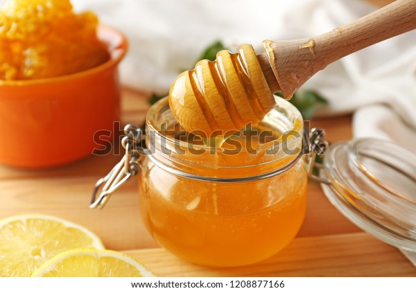 Honey dripping from dipper into jar on table, closeup