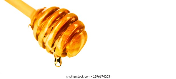 Honey dripping from honey dipper isolated on white background. Thick honey dipping from the wooden honey spoon. Healthy eating concept, diet, dieting. Liquid Syrup, nectar