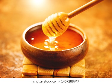 Honey dripping from honey dipper in wooden bowl.  Close-up. Healthy organic Thick honey dipping from the wooden honey spoon, closeup