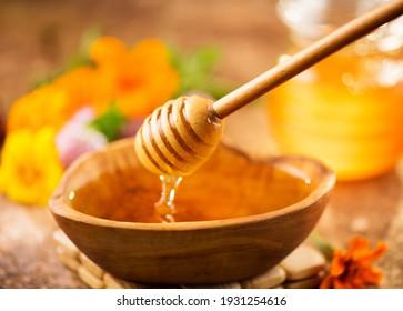 Honig, der aus Honigflossen in einer Holzschüssel tropft.  Nahaufnahme. Gesunde Bio-Dickiger Honigtauchen aus dem Holzhoniglöffel, Nahaufnahme. Blumen und Glas auf dem Tisch