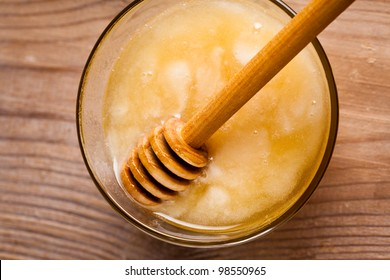 Honey dripping in glass bowl on wooden table