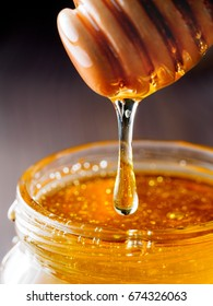 Honey dripping from honey-dipper in glass jar. Extreme closeup