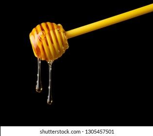 Honey dripping from plastic dipper on black background