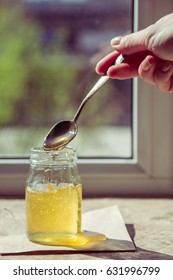 Honey dripping from a spoon. Organic pure honey in jar.