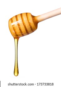 Honey dripping from wooden honey dipper isolated on white background