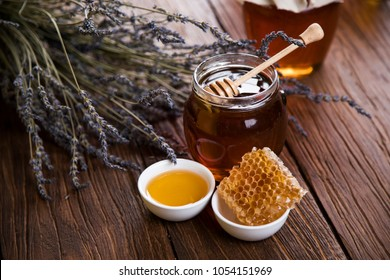Honey dripping from a wooden honey dipper in a jar on wooden background