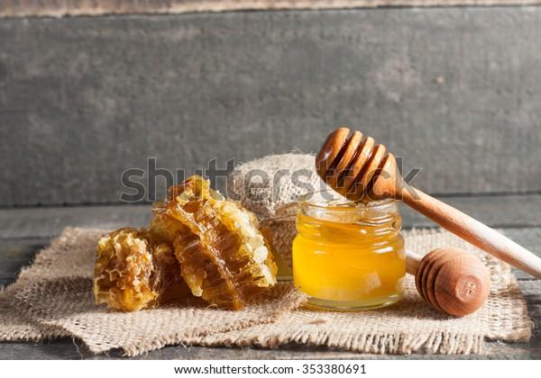 Honig, der von einem Holzhonigabtropfen in einem Glas auf rustikalem Holzhintergrund tropft