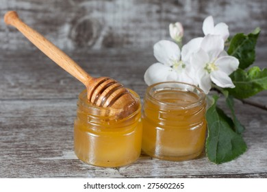 Honey dripping from a wooden honey dipper on wooden grey rustic background