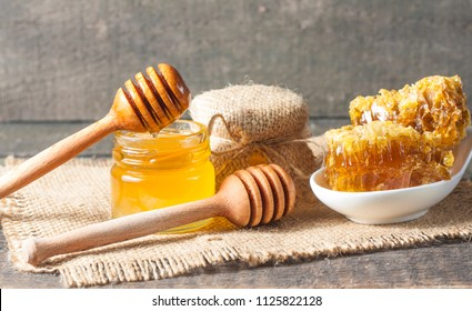 Honey dripping from a wooden honeycomb dipper in a jar on wooden grey rustic background