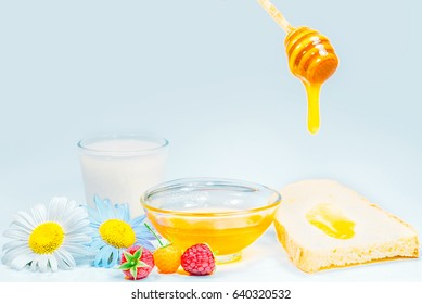 Honey dripping from a wooden spoon, a glass of milk, Fresh honey in a glass bowl on a white background
