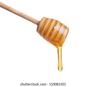 Honey dripping from  wooden  stick isolated on white background