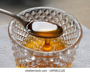 honey drips from a spoon into a crystal vase