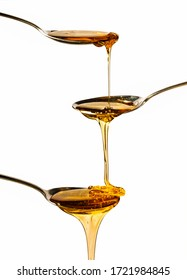 honey falling on metal spoons with a white background