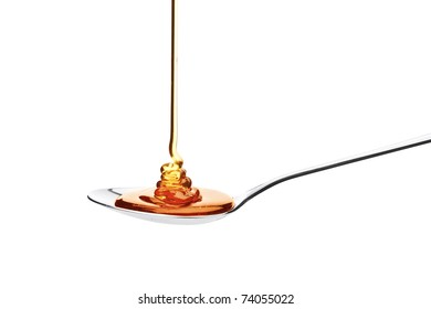 Honey falling on a spoon isolated on white background