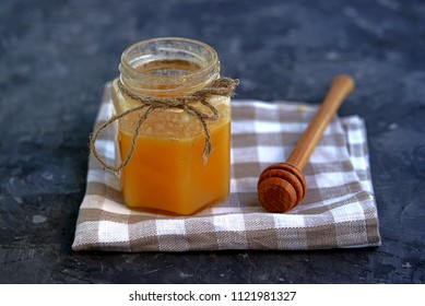 Honey in a figured glass jar, napkin and wooden stick for honey