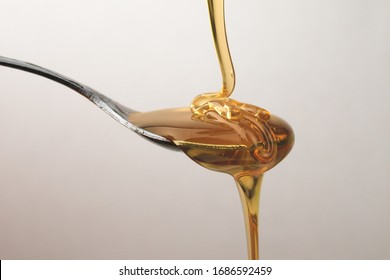 honey flowing down to silver spoon. natural food. sweet desert honey. transparent food. sweet syrup studio light tasty food. beautiful blur background and sharp product.