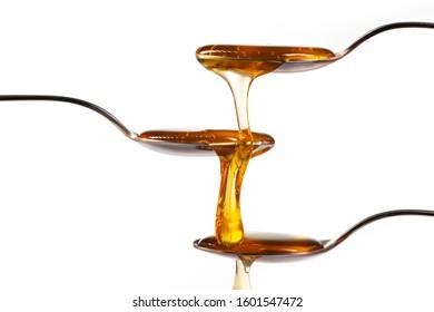 honey flowing from metal spoon