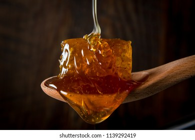 Honey Flows Over Comb in Wooden Spoon in front of dark background