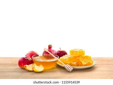 Honey in glass bowl, wooden honey dipper and honeycombs, red apples and garnet on wooden table on a white background with space for text