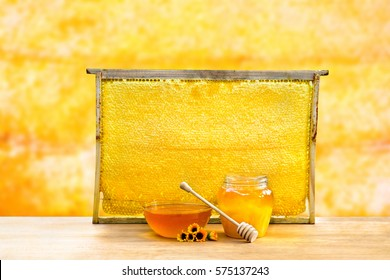 Honey in glass bowl, wooden honey dipper and honeycombs in wooden frame with full cells of honey sealed with wax on wooden table on background honeycombs with full cells of honey