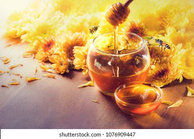 Honey in glass jar with bee flying and flowers on a wooden floor.