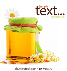 Honey in glass jar with flowers isolated on white background, with sample text
