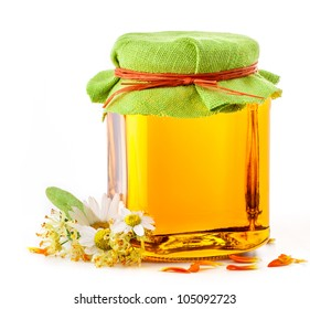 Honey in glass jar with flowers isolated on white background, includes soft shadows