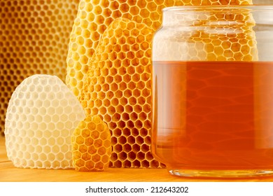 Honey in glass jar, with honeycomb background on wooden rustic tabletop