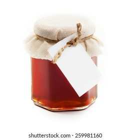 Honey in a glass jar with a label on a white background