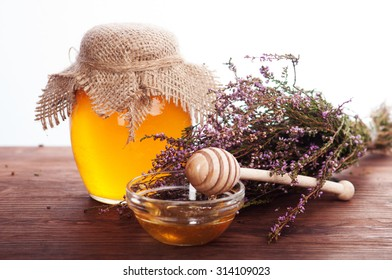 Honey in a glass jar, next to a spoon and a bunch of heather. Vegan concept. White background. Place for writing text