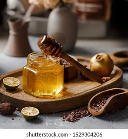 Honey in a glass jar on a gray background next to a  wooden spoon. Honey is poured. Visible texture of honey. Amber color of honey.