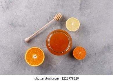 Honey in a glass jar. Set against colds with citrus orange and lemon. View from above.