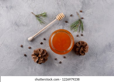 Honey in a glass jar. Set against colds with pine nuts conifer and pine cones. View from above.