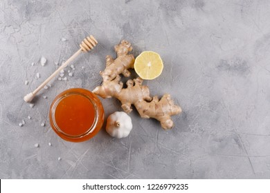 Honey in a glass jar and honey stick. Anti-cold kit with garlic ginger and lemon. View from above.