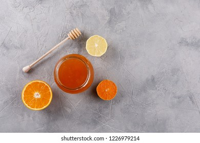 Honey in a glass jar and honey stick. Set against colds with citrus orange and lemon. View from above.