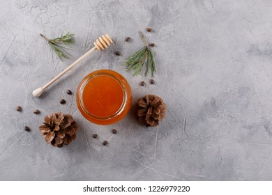 Honey in a glass jar and honey stick. Set against colds with pine nuts conifer and pine cones. View from above.