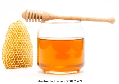 Honey in glass jar with wooden dipper and honeycomb on white isolated background