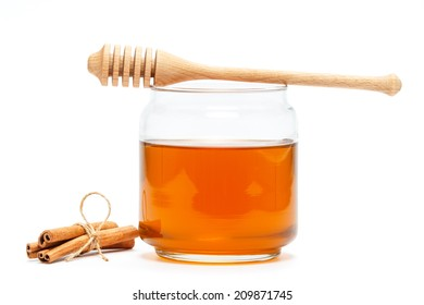 Honey in glass jar with wooden dipper and cinnamon sticks on white isolated background