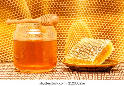 Honey in glass jar with wooden dipper and honeycomb on light rustic mat with honeycomb background