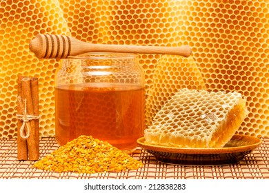 Honey in glass jar with wooden dipper, honeycomb, pollen granules and cinnamon sticks on light rustic mat with honeycomb background