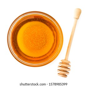 Honey in a glass plate with a wooden stirrer on a white. The view of the top.