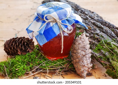 Honey glass pot with young pine on a wooden background