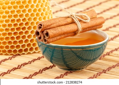 Honey in green porcelain bowl, with honeycomb and cinnamon sticks on light rustic mat