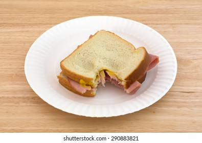 A honey ham sandwich with mustard on white bread that has been bitten upon a paper plate and wood table top.