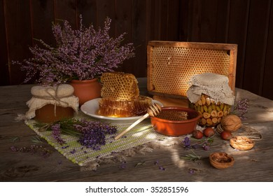 Honey, honeycomb, nuts and flowers on the wooden table