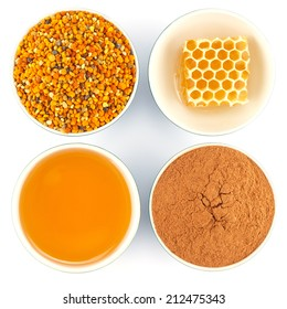 Honey, honeycomb, pollen granules and cinnamon in porcelain bowls, seen from above, on white isolated background