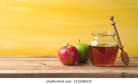 Honey jar and apples on wooden table. Jewish holiday Rosh Hashanah background