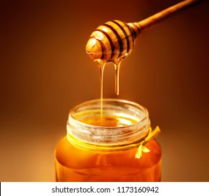Honey in jar with honey dipper on rustic wooden table background. Copy space.