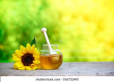 Honey in jar with dipper and sunflower on wooden background